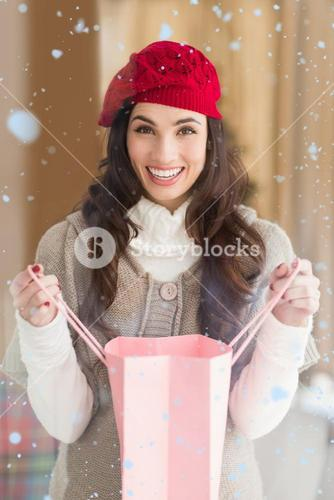Composite image of happy brunette opening gift bag