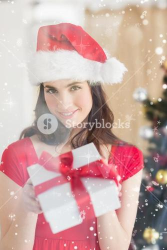 Composite image of beauty brunette showing gift at christmas