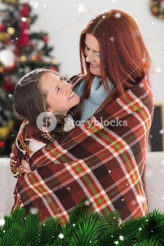 Composite image of festive mother and daughter wrapped in blanket