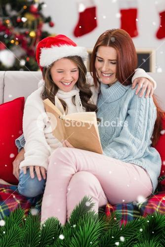 Composite image of festive mother and daughter reading on the couch