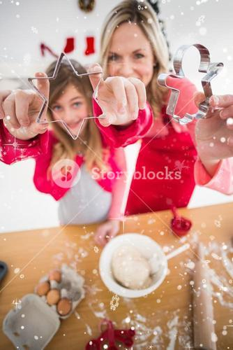 Composite image of festive mother and daughter making christmas cookies