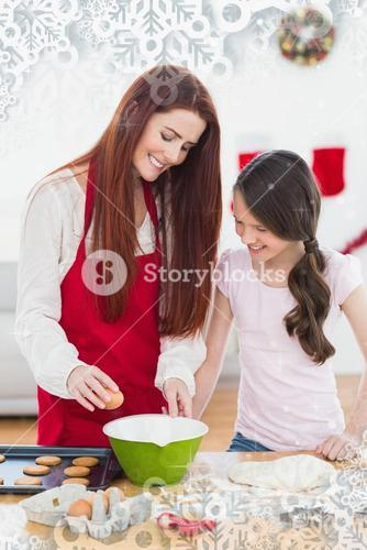 Composite image of festive mother and daughter baking together