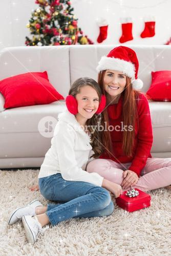 Composite image of festive mother and daughter opening a christmas gift