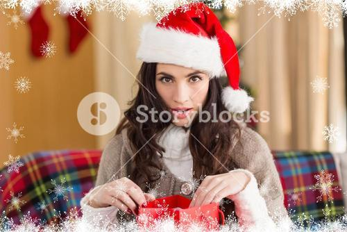 Composite image of surprised brunette opening gift bag at chistmas