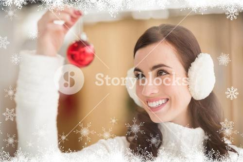 Composite image of pretty brunette with ear muffs holding bauble