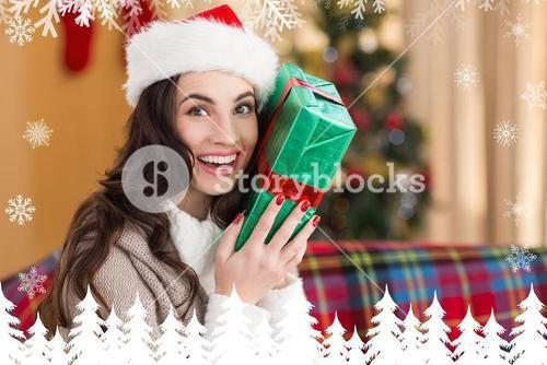 Composite image of festive brunette holding gift at christmas