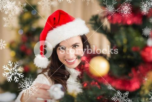Composite image of beauty brunette decorating a christmas tree