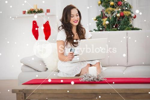 Composite image of pretty brunette shopping online with laptop at chistmas