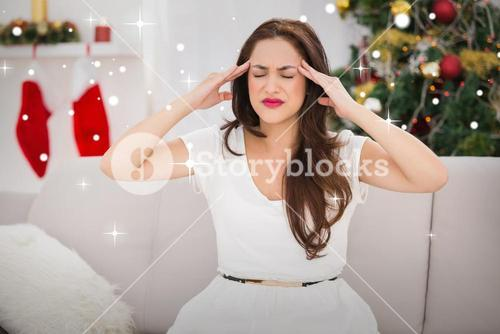Composite image of brunette getting a headache on christmas day