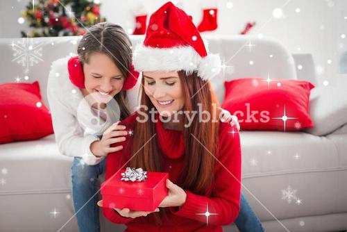 Composite image of festive mother and daughter with a christmas gift