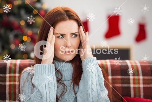 Composite image of woman getting a head ache at christmas