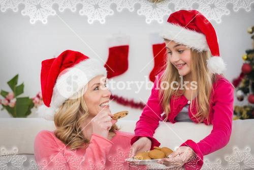 Composite image of festive mother and daughter with plate of cookies