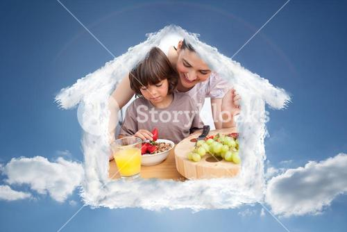 Composite image of jolly mother and her child having breakfast