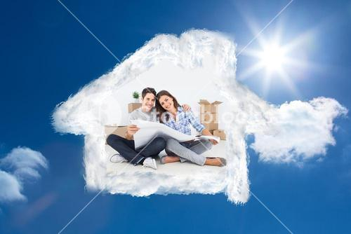 Composite image of man and woman holding house plans