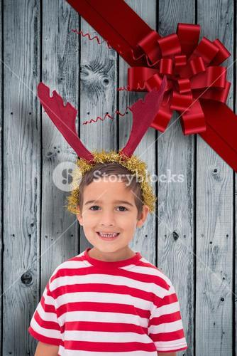 Composite image of cute little boy wearing antlers