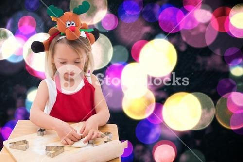 Composite image of festive little girl making cookies