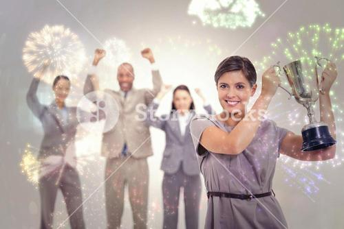 Composite image of woman holding up a cup with enthusiastic coworkers