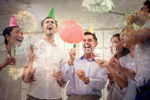 Composite image of casual business team celebrating with champagne and party horns