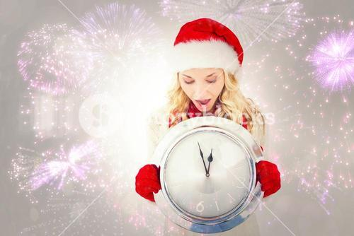Composite image of festive blonde holding large clock