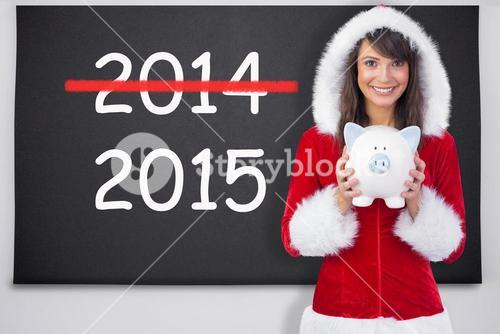 Composite image of smiling brunette in santa claus holding a piggy bank