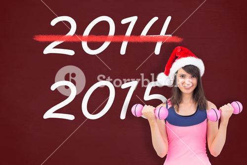 Composite image of woman in santa hat holding hand weight