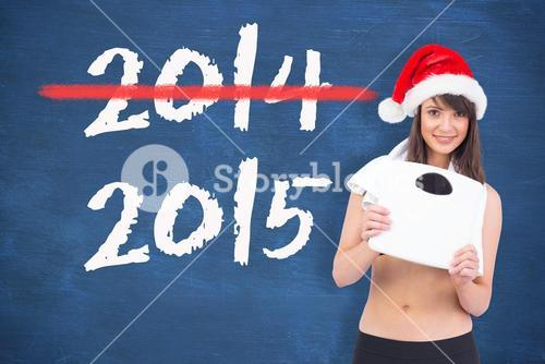 Composite image of festive fit brunette holding a weighing scales
