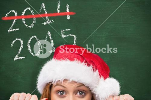 Composite image of festive redhead smiling at camera holding poster