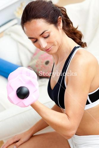 Young athletic woman holding a dumbbell in her livingroom