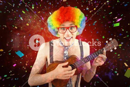 Composite image of geeky hipster in afro rainbow wig playing guitar