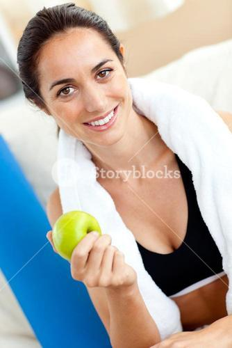 Radiant woman eating an apple on the sofa after working out in the livingroom