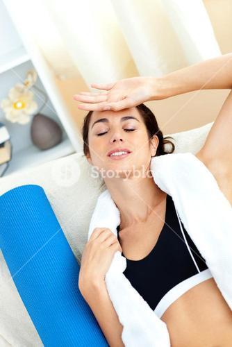 Tired woman sitting on a sofa after working out in her livingroom