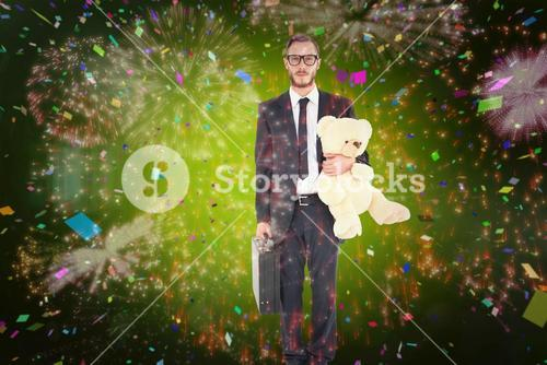 Composite image of geeky businessman holding briefcase and teddy