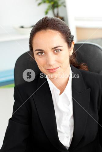 Assertive businesswoman looking at the camera sitting in her office