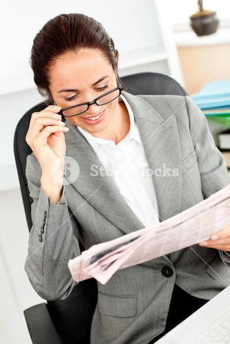 Delighted young businesswoman holding glasses reading a newspaper in her office