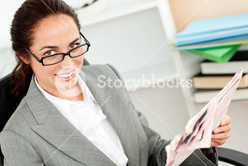 Joyful businesswoman wearing glasses and holding a newspaper in her office