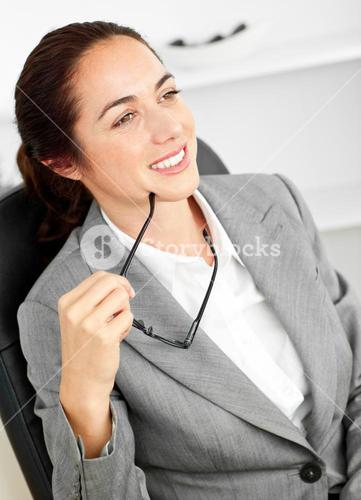 Assertive businesswoman holding her glasses sitting in her office