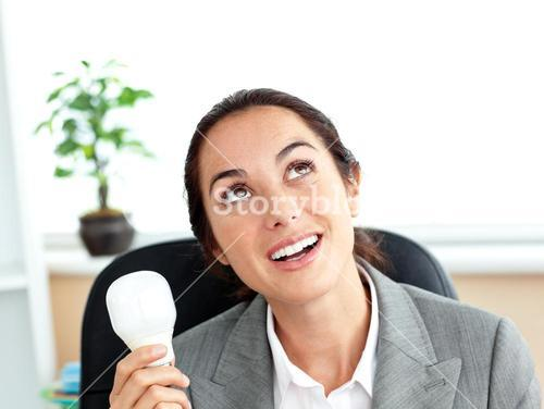 Surprised businesswoman holding a light bulb sitting in her office