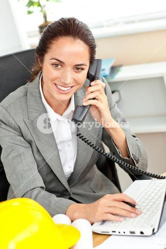 Confident female architect talking on phone and using her laptop in her office