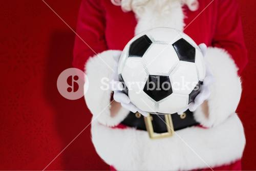 Composite image of mid section of santa holding football