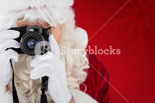 Composite image of portrait of santa taking a photo