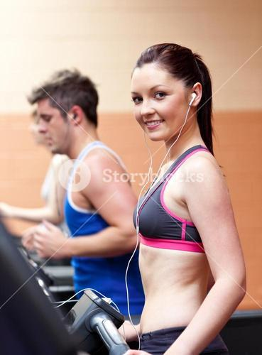 Cute athletic woman standing on a running machine with earphones