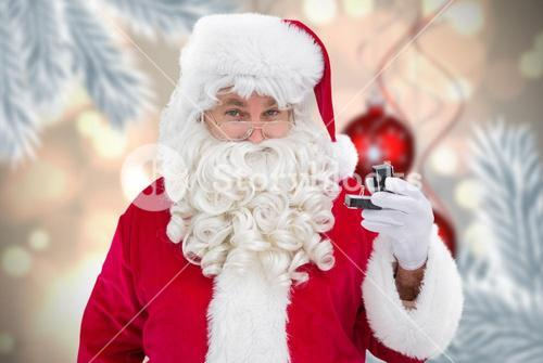 Composite image of cheerful santa holding a jewelry box