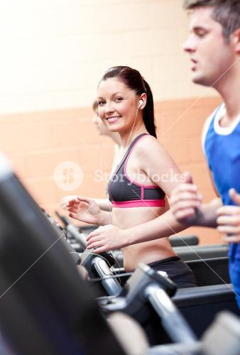 Cute athletic woman with earphones exercising on a running machine