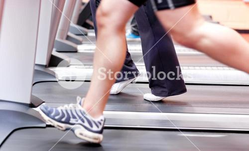 Close up of the legs of an athletic young woman exercising on a running machine