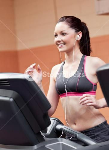 Smiling athletic woman training on a running machine with earphones