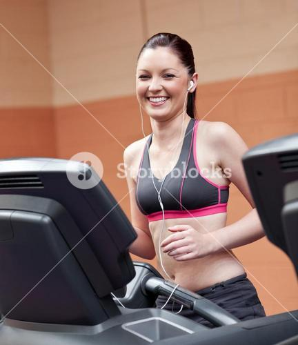 Radiant athletic woman with earphones exercising on a running machine