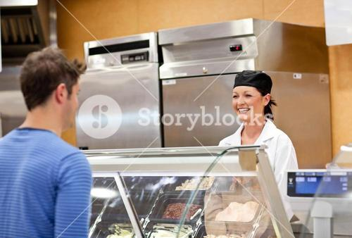Portrait of a smiling food retailer with a male customer