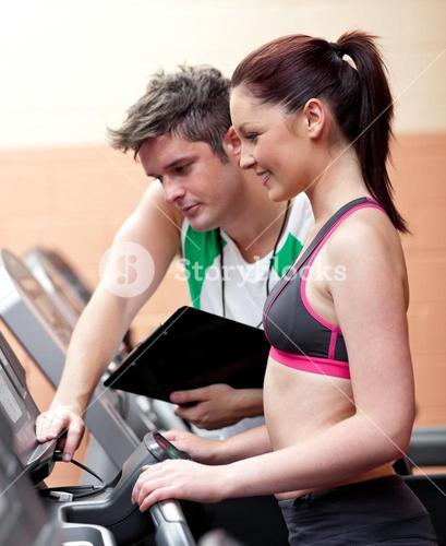 Beautiful athletic woman standing on a running machine with her personal coach