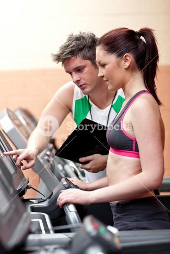 Beautiful female athlete standing on a running machine talking with her personal coach