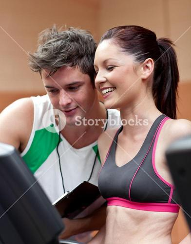 Cheerful athletic woman standing on a running machine with her personal coach